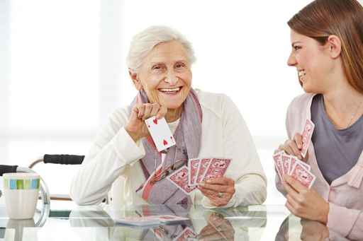 Frau spielt mit Seniorin im Seniorenheim Karten
